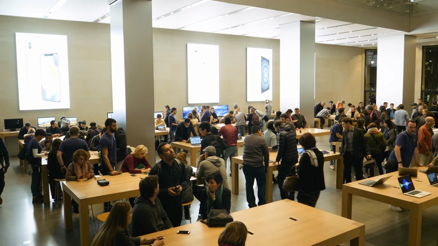 macintosh : BARCELONA, SPAIN - CIRCA 2019: elevated pan over hundreds of customers people inside Apple Store Passeig de Gracia admiring latest technology gadgets by Cupertino Apple Computers Stock Footage