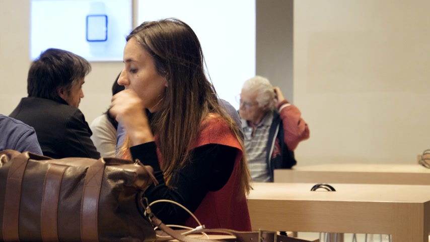 macintosh : BARCELONA, SPAIN - CIRCA 2019: Zoom out from adult woman as customers people inside Apple Store Passeig de Gracia waiting for their education course Genius Bar and Support and Today at Apple Stock Footage