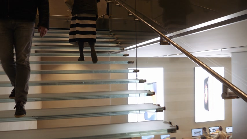 macintosh : BARCELONA, SPAIN - CIRCA 2019: POV climbing iconic glass stairs customers people inside Apple Store Passeig de Gracia admiring latest technology gadgets by  Apple Computers