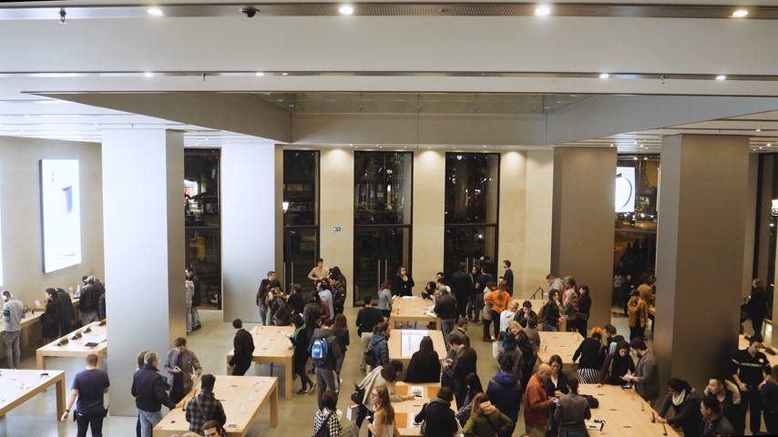 macintosh : BARCELONA, SPAIN - CIRCA 2019: Elevated view scene of customers people inside Apple Store Passeig de Gracia admiring latest technology gadgets by Cupertino giant Apple Computers Stock Footage
