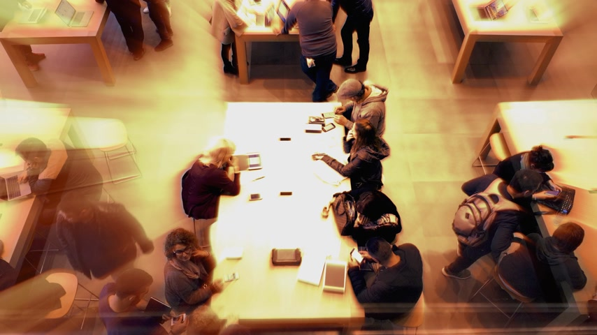 производитель : BARCELONA, SPAIN - CIRCA 2019: Radiating light beam from customers people inside Apple Store Passeig de Gracia admiring latest technology gadgets by Cupertino giant Apple Computers