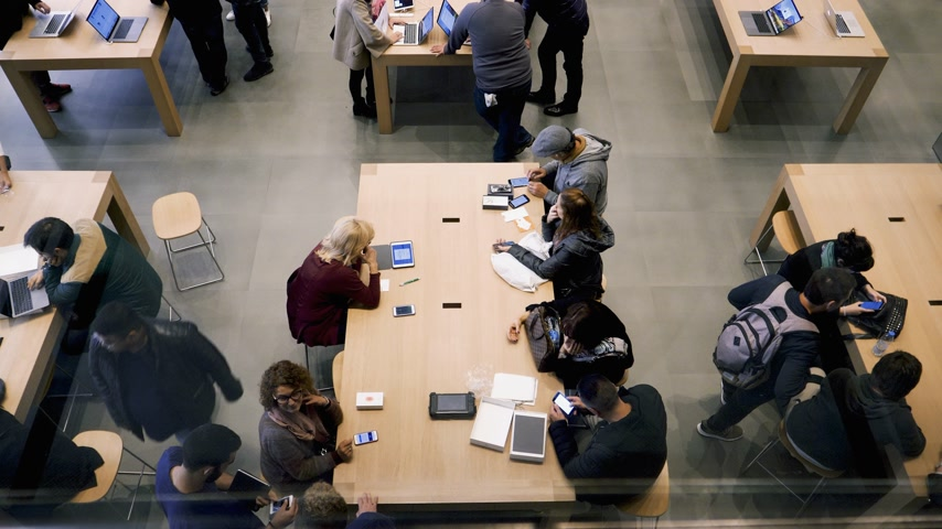 deha : BARCELONA, SPAIN - CIRCA 2019: Elevated view of customers people inside Apple Store Passeig de Gracia receiving help  by Genius employee for iPhone iPad and mac purchase