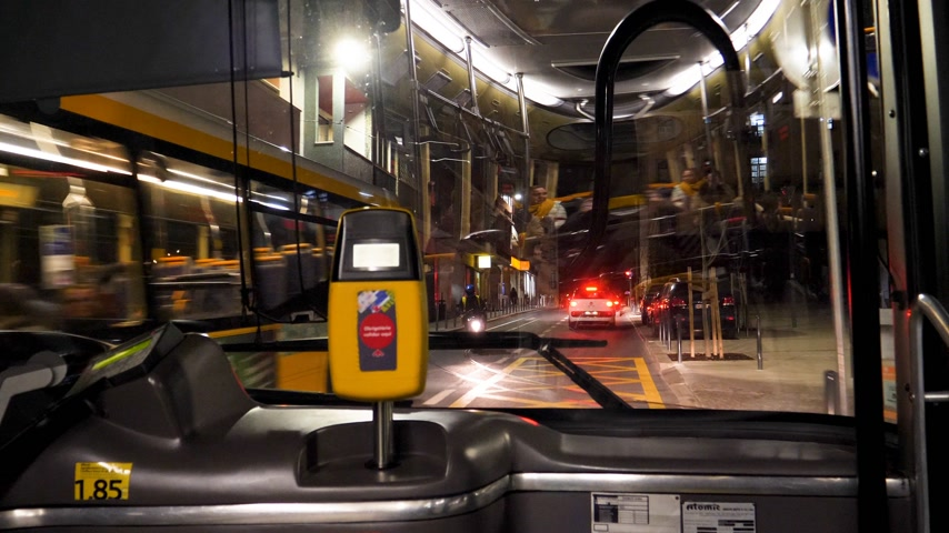 inside bus : LISBON, PORTUGAL - CIRCA 2019: Time lapse fast motion with beautiful view of the Lisbon street at night from front window of public transportation bus first row seats