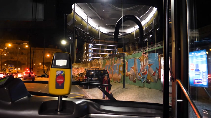 inside bus : LISBON, PORTUGAL - CIRCA 2019: Time lapse fast motion with bus approaching station in Lisbon man enters pay for ticket Lisbon street at night from front window of public transportation bus first row seats