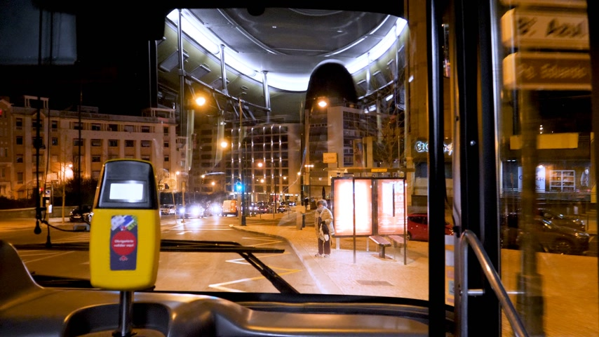 inside bus : LISBON, PORTUGAL - CIRCA 2019: Beautiful view of the Lisbon street at night from front window of public transportation bus first row seats adult woman at bus station enter bus Stock Footage