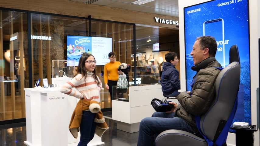 corte : LISBON, PORTUGAL - CIRCA 2019: Father and daughter having a convivial mont inside El Corte Ingles technological electronics department with man trying out the VR helmet