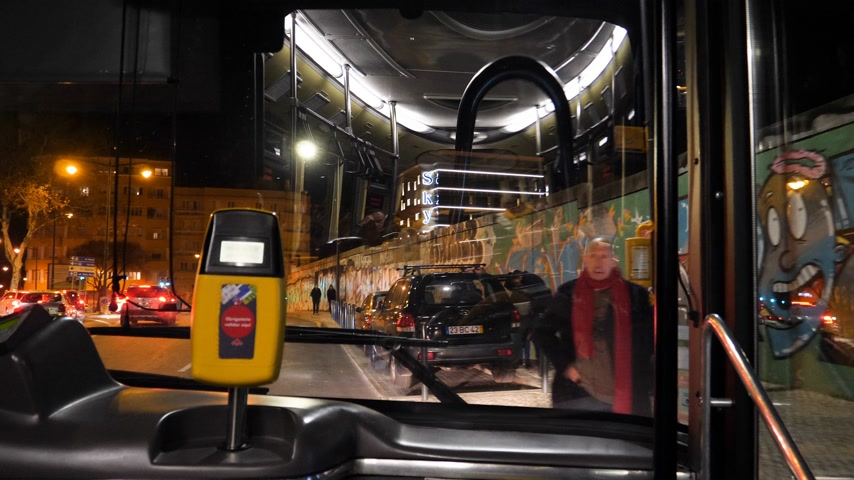 inside bus : LISBON, PORTUGAL - CIRCA 2019: Beautiful view of the Lisbon street at night from front window of public transportation bus first row seats adult man enters at bus station