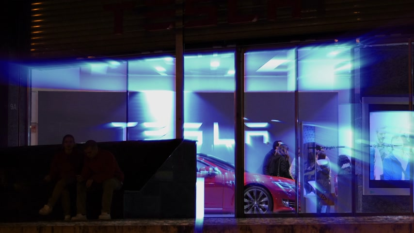 tesla model s : LISBON, PORTUGAL - CIRCA 2018: Radiating iridescent beam light from Tesla logo with customers inside car dealer shopping new electric car from Tesla Motors inside showroom El Corte Ingles on Av. Antonio Augusto de Aguiar 31