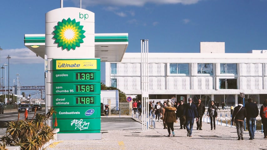 franczyza : LISBON, PORTUGAL - CIRCA 2019: Cinematic colored slow motion people walk near BP British Petroleum gas station on Av. Brasilia Doca Bom Sucesso boulevard - digital prices for gas, petrol, gasoline gas and diesel