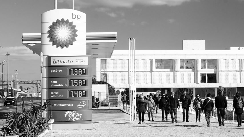 franczyza : LISBON, PORTUGAL - CIRCA 2019: Slow motion people walk near BP British Petroleum gas station on Av. Brasilia Doca Bom Sucesso boulevard - digital prices for gas, petrol, gasoline gas and diesel black and white Wideo