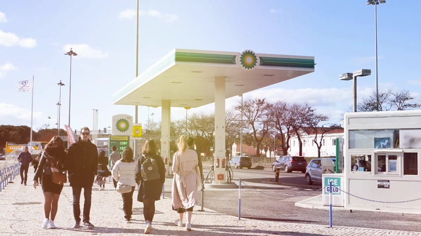 cadeia : LISBON, PORTUGAL - CIRCA 2019: Sunlight flare slow motion people walk near BP British Petroleum gas station on Av. Brasilia Doca Bom Sucesso boulevard