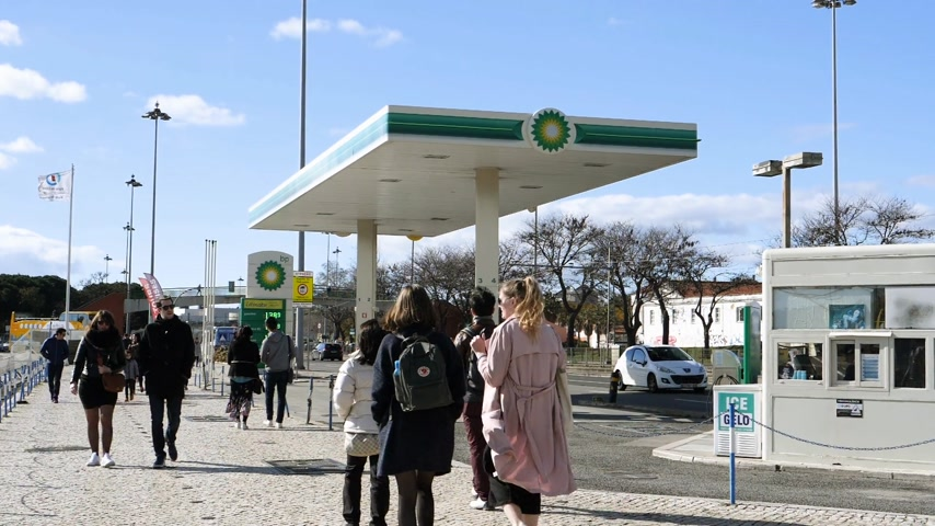 franczyza : LISBON, PORTUGAL - CIRCA 2019: Time lapse fast motion people walk near BP British Petroleum gas station on Av. Brasilia Doca Bom Sucesso boulevard - digital prices on the background board Wideo