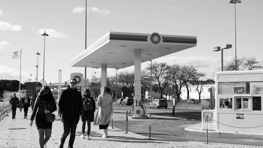 бульвар : LISBON, PORTUGAL - CIRCA 2019: Slow motion people walk near BP British Petroleum gas station on Av. Brasilia Doca Bom Sucesso boulevard - black and white HD footage