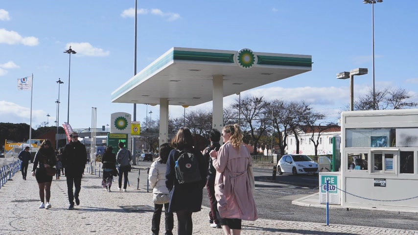 franczyza : LISBON, PORTUGAL - CIRCA 2019: Slow motion people walk near BP British Petroleum gas station on Av. Brasilia Doca Bom Sucesso boulevard - digital prices for gas, petrol, gasoline gas and diesel