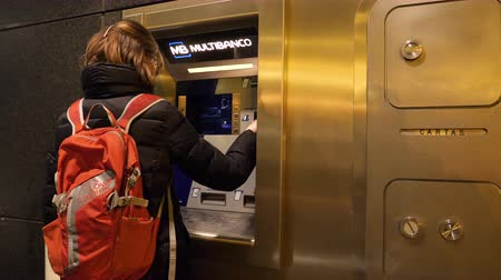 bankomat : LISBON, PORTUGAL - CIRCA 2019: Woman insert card in Multibanco ATM Automatic teller machine at night in central Lisbon near bank branch withdrawing money from the bank