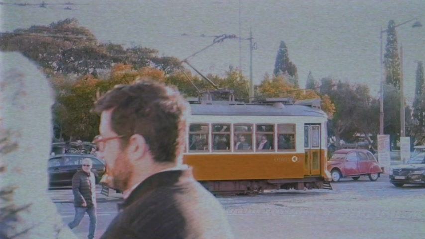 retro revival : LISBON, PORTUGAL - CIRCA 2019: Cinematic city scene Remodelado tram nearby Mosteiro dos Jeronimos in Praca do Imperio people pedestrians walking at sunset vhs vintage film tape sightseeing Lisbon Stock Footage