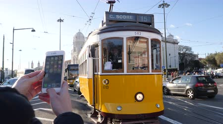 comercio : LISBON, PORTUGAL - CIRCA 2019: Female tourist using iPhone smartphone to take photo of Remodelado tram with Mosteiro dos Jeronimos in the background in Praca do Imperio