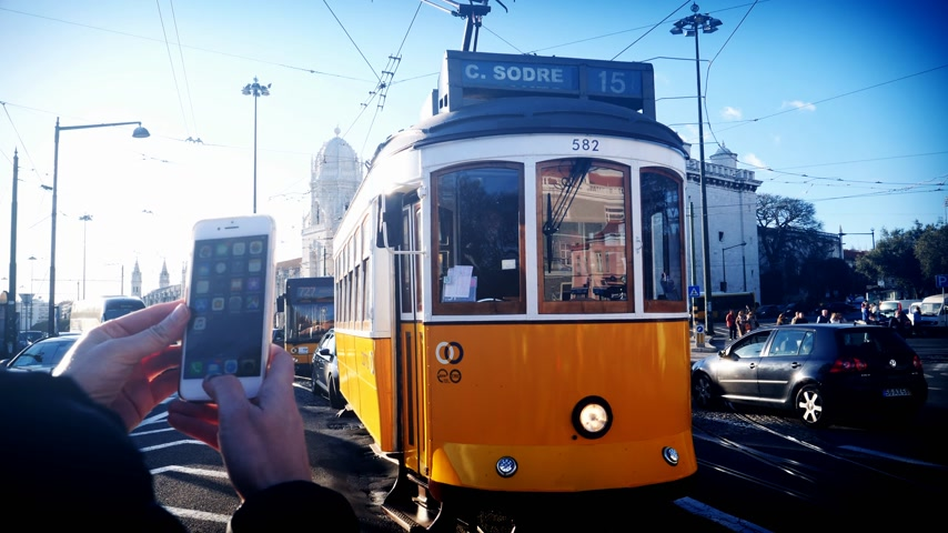 comercio : LISBON, PORTUGAL - CIRCA 2019: Female tourist using iPhone smartphone to take photo of Remodelado tram with Mosteiro dos Jeronimos in the background in Praca do Imperio cinematic vidvid colours