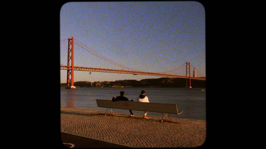 подвесной : LISBON, PORTUGAL - CIRCA 2019: Rear view of male couple admiring the sunset over Tagus river with majestic 25 de Abril Bridge Ponte 25 de Abril Salazar smoking a cigar joint vhs square old film effect