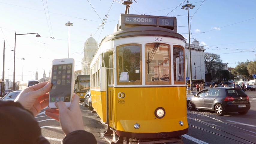comercio : LISBON, PORTUGAL - CIRCA 2019: Female tourist using iPhone smartphone to take photo of Remodelado tram with Mosteiro dos Jeronimos in the background in Praca do Imperio sunlight flare Stock Footage