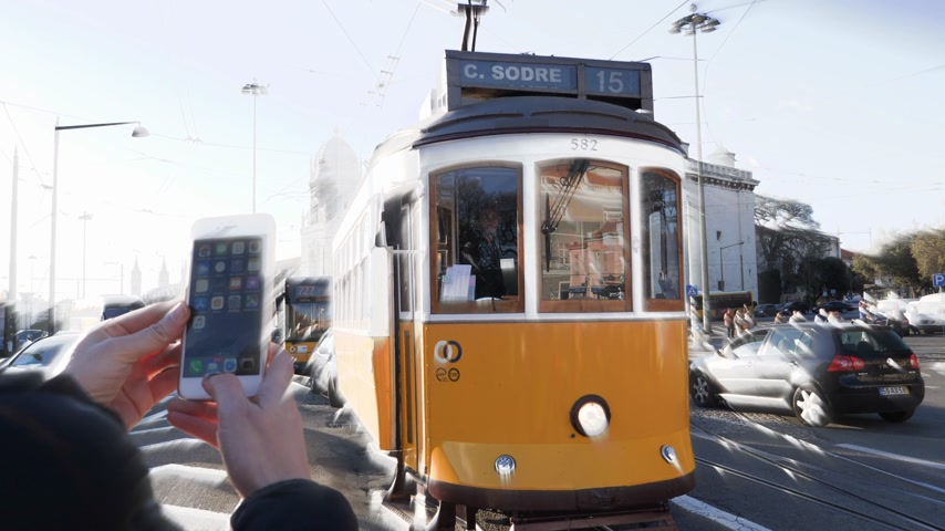 comercio : LISBON, PORTUGAL - CIRCA 2019: Female tourist using iPhone smartphone to take photo of Remodelado tram with Mosteiro dos Jeronimos in the background in Praca do Imperio sunlight iridescent light