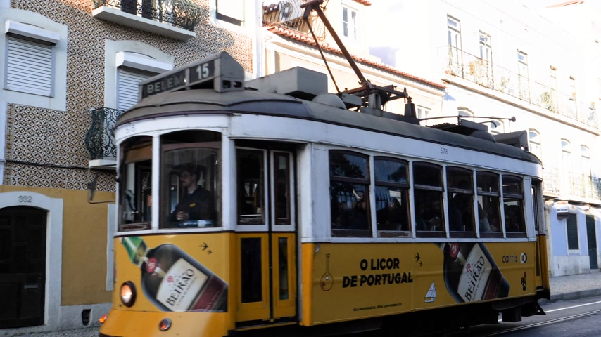 sto : LISBON, PORTUGAL - CIRCA 2019: Full with passengers Remodelado tramway 15 driving on the R. da Junqueira street in Lisbon with Tramway station full two people in the background