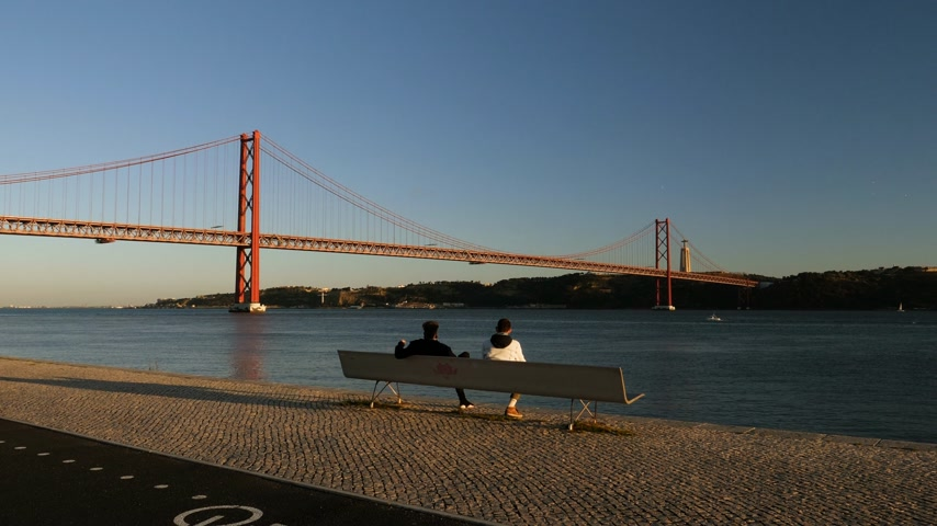 the suspension bridge : LISBON, PORTUGAL - CIRCA 2019: Rear view of male couple admiring the sunset over Tagus river with majestic 25 de Abril Bridge Ponte 25 de Abril Salazar smoking a cigar joint