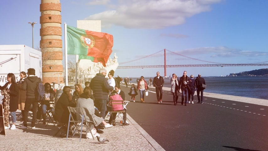 the suspension bridge : LISBON, PORTUGAL - CIRCA 2019: Group of portuguese people having an reunion near Ponte 25 de Abril bridge with pedestrians walking nearby - slow motion cinematic flare Stock Footage