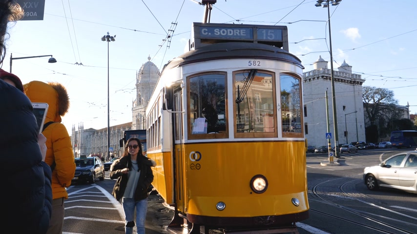 retro revival : LISBON, PORTUGAL - CIRCA 2019: Asian tourist asking for a free place in the Remodelado tramway in Praca do Imperio with Mosteiro dos Jeronimos in the background beautiful sunset light 4k UHD