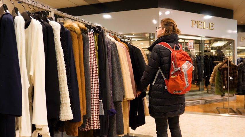 corte : LISBON, PORTUGAL - 2019: Young woman with red backpack shopping for the luxury coats in the El Corte Ingles mall Pele fashion brand