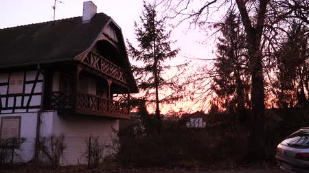 half timbered : Quatzenheim Alsace, France - Circa 2019:  sunset over traditional Alsatian timbered house a few steps from old Jewish cemetery with nearby parked Peugeot car