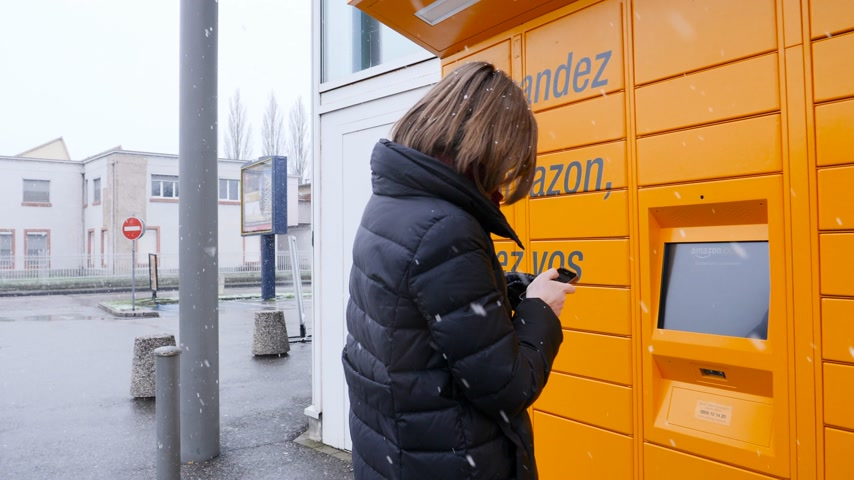バーコード : Strasbourg, France - Feb 8, 2018: Young woman using yellow Amazon Locker the self-service parcel delivery service station near Auchan supermarket touchscreen code press on display from smartphone 動画素材