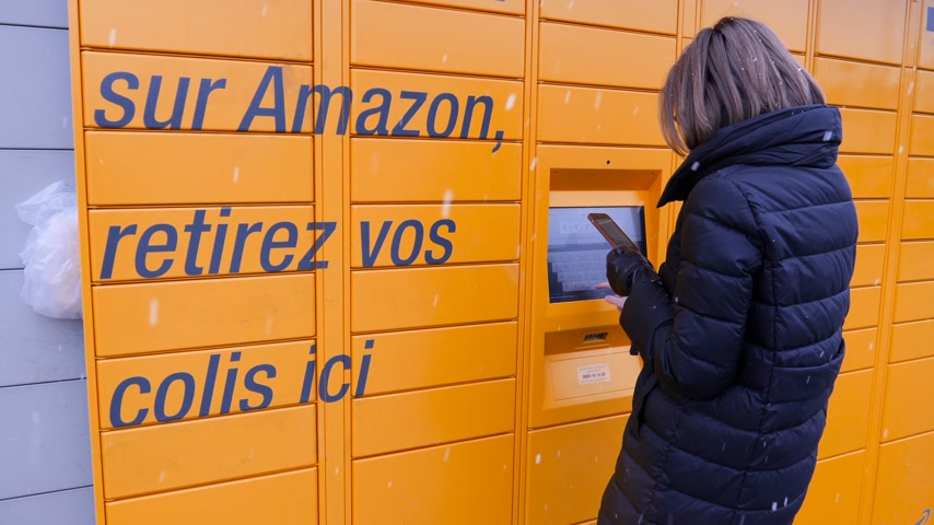 バーコード : Strasbourg, France - Feb 8, 2018: Side view of young woman using yellow Amazon Locker the self-service parcel delivery service station near Auchan supermarket touchscreen code press on display