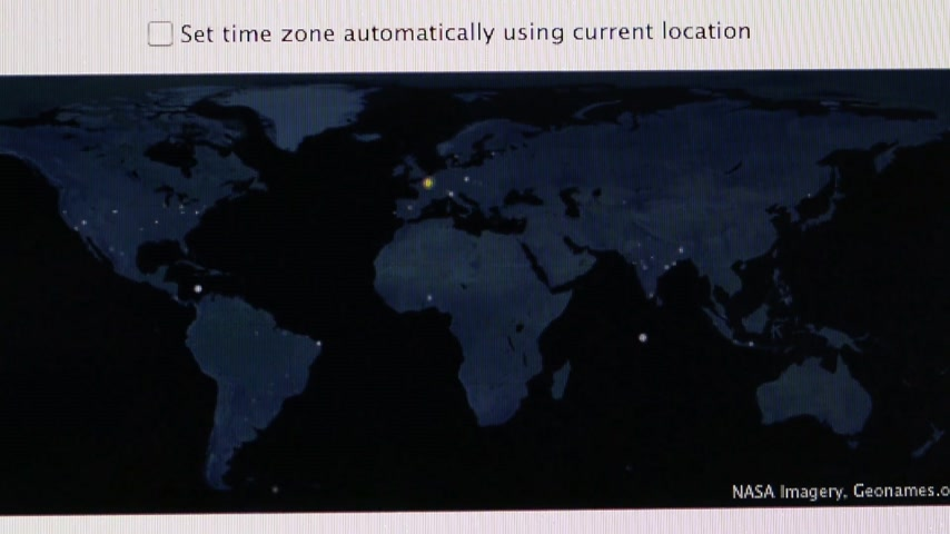 apple sign : CALIFORNIA, UNITED STATES - CIRCA 2014: Apple Computers new desktop computer iMac with settings of the time zone on world map during initial setup of the Mac Os X software Stock Footage