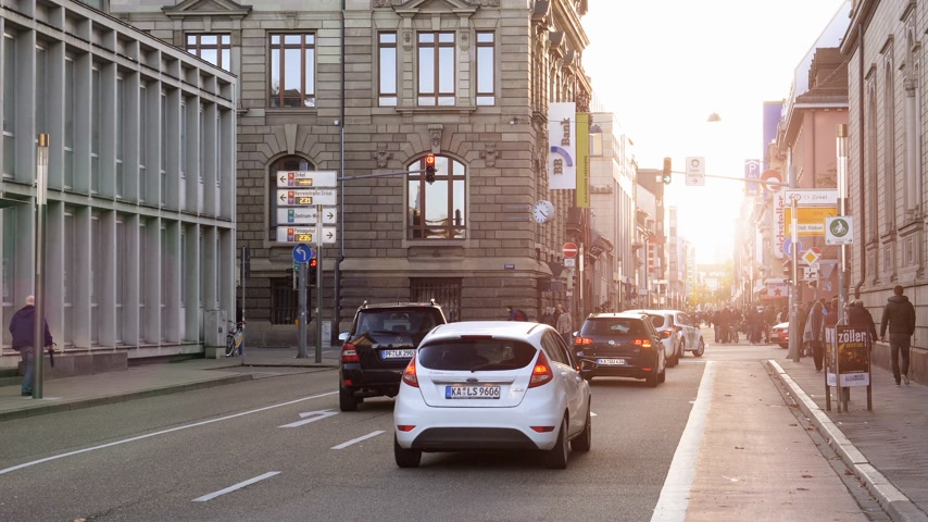 hostující : Karlsruhe, Germany - Oct 29, 2017: Sunset sunlight flare on Waldstrasse street with pedestrians, cars, BB bank sign visiting the German city Dostupné videozáznamy