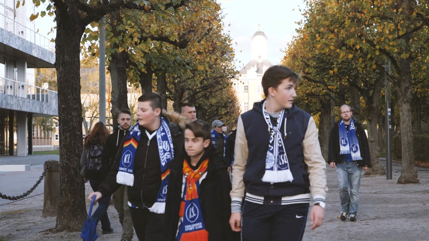 nakládané : Karlsruhe, Germany - Circa 2018: Adult and young male supporters fans walking in central park with Karlsruher Sport-Club Muhlburg-Phonix e. V insignia scarfs