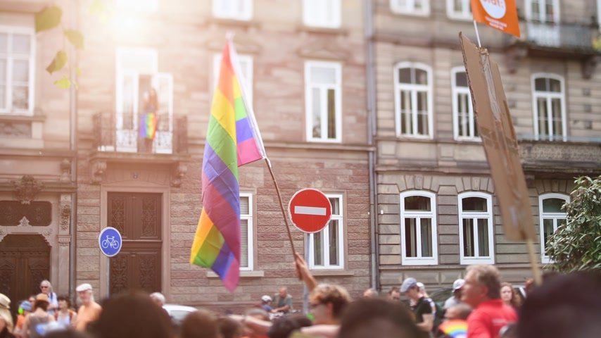 sexualita : Tilt-shift defocused crowd waving rainbow flags at annual FestiGays pride gays and lesbians parade marching French streets dancing fun party atmosphere Free hugs placard cinematic flare