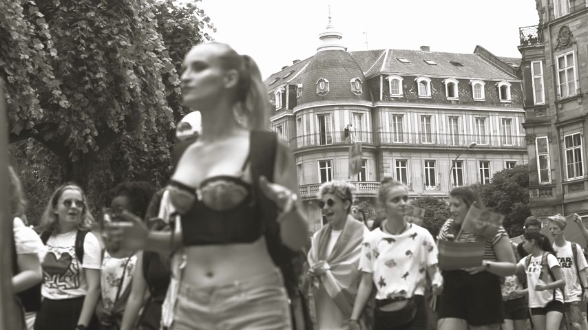 tilt shift : STRASBOURG, FRANCE - CIRCA 2018: Monochrome footage of people waving rainbow flags at annual FestiGays pride gays and lesbians parade marching on French streets dancing fun party atmosphere perspective view