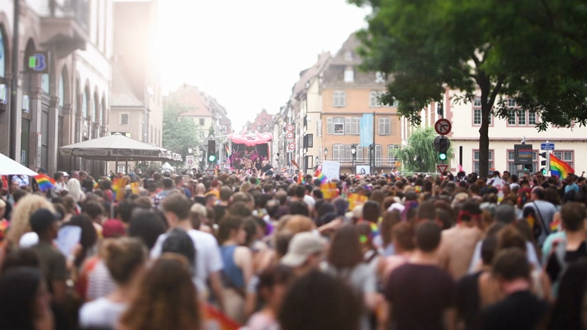 tilt shift : STRASBOURG, FRANCE - CIRCA 2018: Cinematic flare over large crowd of people following gay pride truck at annual FestiGays pride gays and lesbians parade marching French streets dancing fun party atmosphere