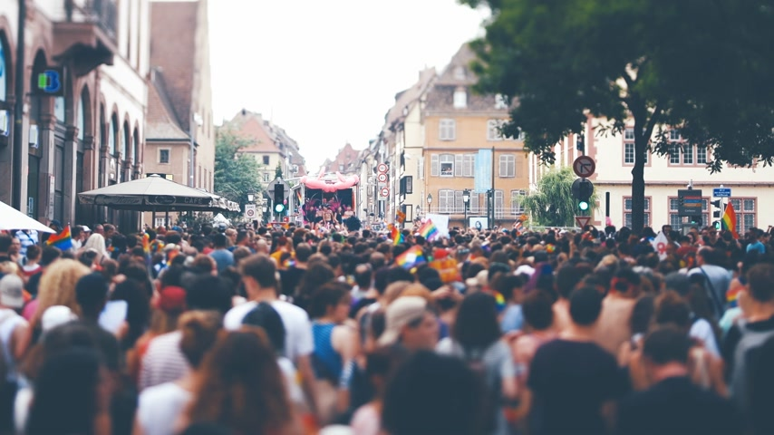 tilt : STRASBOURG, FRANCE - CIRCA 2018: Cinematic color grading over large crowd of people following gay pride truck at annual FestiGays pride gays and lesbians parade marching French streets dancing fun party atmosphere