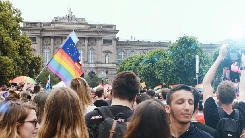 haklar : STRASBOURG, FRANCE - CIRCA 2018: Bright sunlight cinematic flare over large crowd of people waving rainbow LGBT, Eu and NATO flags at annual FestiGays pride parade marching in front University Stok Video