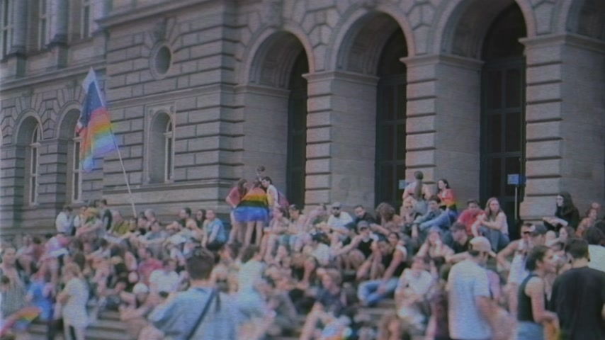 haklar : STRASBOURG, FRANCE - CIRCA 2018: Gay, EU, UN and French flag waving over crowd resting on stairs of Strasbourg University building before the annual Gay pride FestiGays march VHS film effect Stok Video