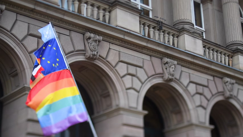sexualita : United Nations, European union, French National and German national flags waving on the same flagpole with LGBT rainbow flag at annual pride march demonstration with old French building in the background Dostupné videozáznamy