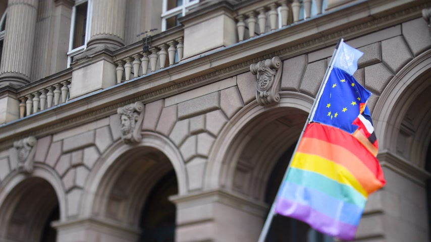 sexualité : United Nations, European union, French National and German national flags waving on the same flagpole with LGBT rainbow flag at annual pride march demonstration with old French building in the background Vidéos Libres De Droits