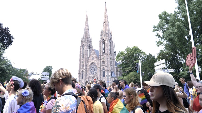 sexualité : STRASBOURG, FRANCE - CIRCA 2018: Large crowd of people waving rainbow flags at annual FestiGays pride happy gays and lesbians parade marching in front of Reformed Church Saint Paul slow motion Vidéos Libres De Droits