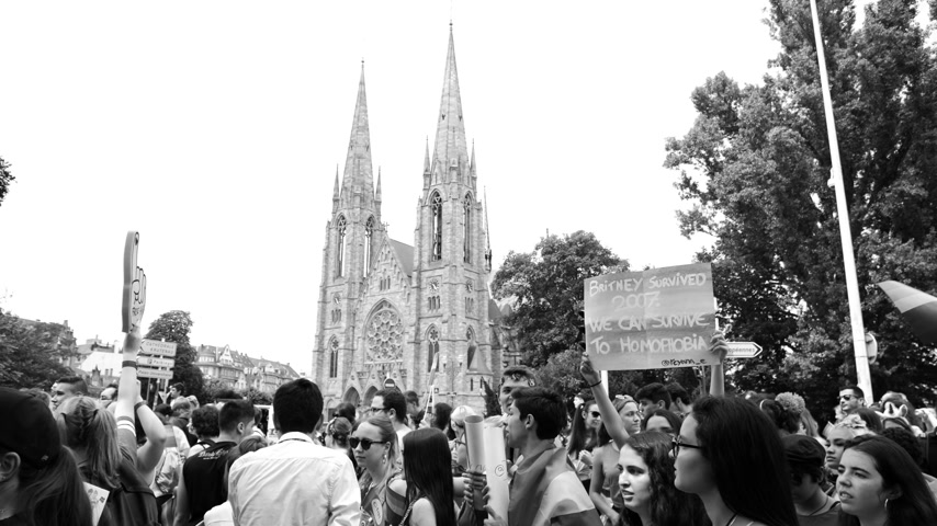 seksualiteit : STRASBOURG, FRANCE - CIRCA 2018: Monochrome footage of people at annual FestiGays pride happy gays and lesbians parade marching in front of Reformed Church Saint Paul slow motion