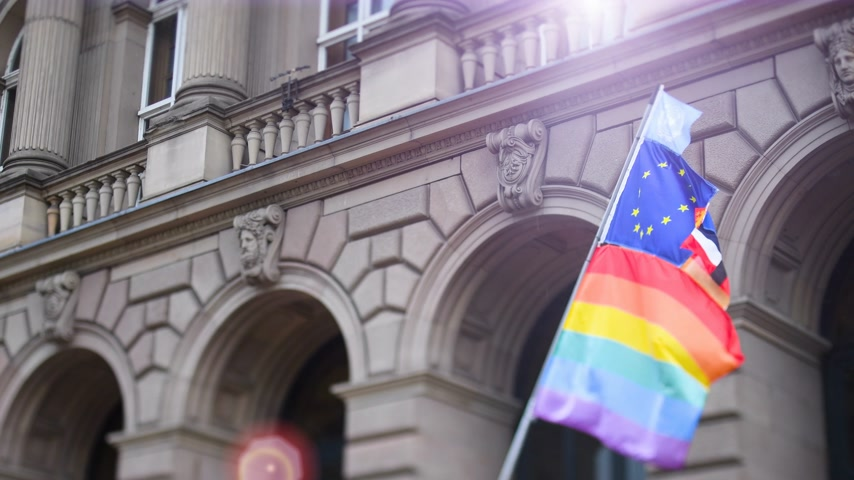 gurur : Sunlight flare beam over United Nations, European union, French National and German national flags waving on the same flagpole with LGBT rainbow flag at annual pride march demonstration with old French building in the background Stok Video