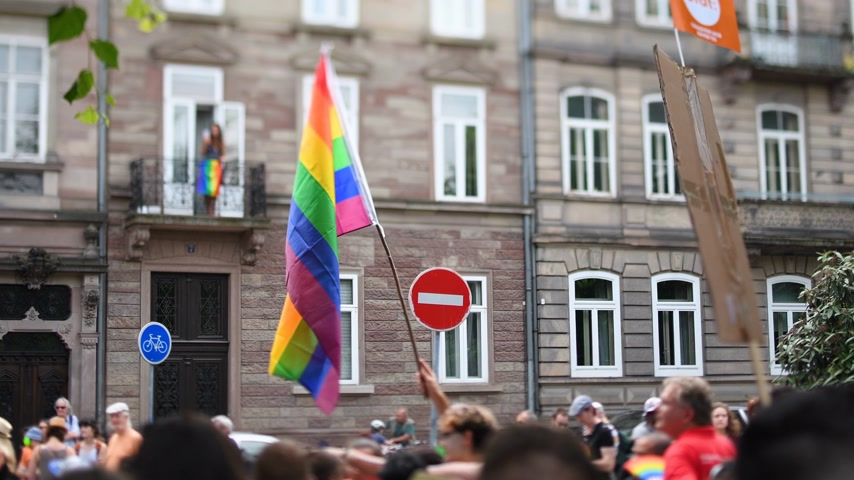 tilt shift : Tilt-shift defocused crowd waving rainbow flags at annual FestiGays pride gays and lesbians parade marching French streets dancing fun party atmosphere Free hugs placard Stock Footage