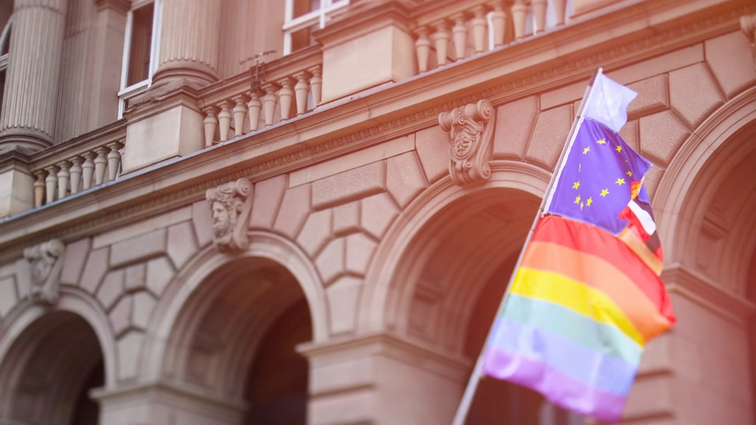 união europeia : Warm cinematic flare over United Nations, European union, French National and German national flags waving on the same flagpole with LGBT rainbow flag at annual pride march demonstration