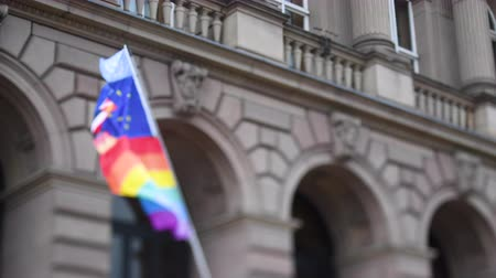 união europeia : United Nations, European union, French National and German national flags waving on the same flagpole with LGBT rainbow flag at annual pride march demonstration with old French building in the background Stock Footage